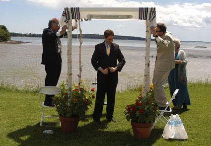the groom put up the huppah wedding canopy photo by Robert Neudel